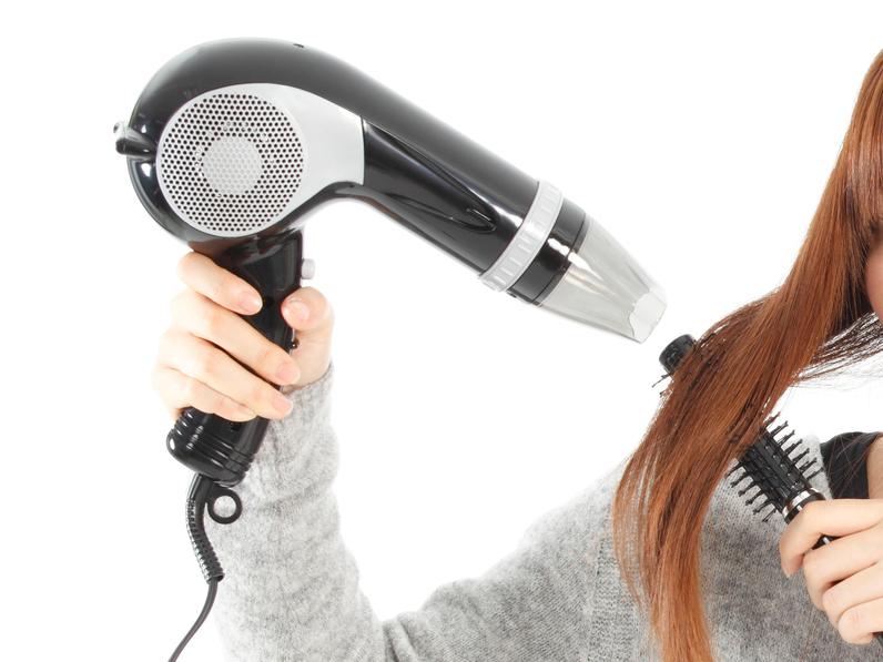 ドライヤーで髪をブローする女性